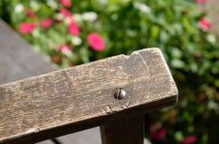 Nahaufnahme des alten verwitterten Schaukelstuhl-Armes mit Blumen im Hintergrund Lizenzfreie Stockbilder