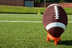 Nahaufnahme des amerikanischen Fußballs auf T-Stück auf Feld Lizenzfreie Stockfotos