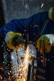 Nahaufnahme des Arbeitskraftausschnittmetalls mit Schleifer Funkt beim Reiben des Eisens Lizenzfreies Stockfoto