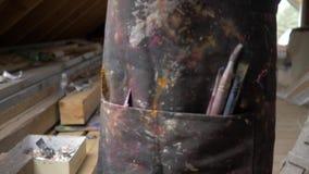 Nahaufnahme des Arbeitsschutzblechs des Künstlers, in deren Taschen die Bürste liegen 4K stock footage