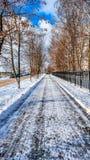 Nahaufnahme des Asphalts im Schnee Straße des blauen Himmels in der Stadt im Winter, gesäuberter Schnee bürstete Straße vom Schne Stockbild