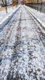 Nahaufnahme des Asphalts im Schnee Straße in der Stadt im Winter, gesäuberter Schnee säuberte die Straße vom Schnee in Lizenzfreies Stockfoto
