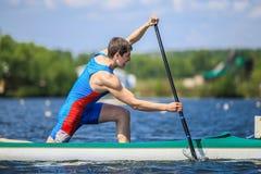 Nahaufnahme des Athletenkanufahrerrudersports mit einem Ruder in einem Kanu Stockbilder