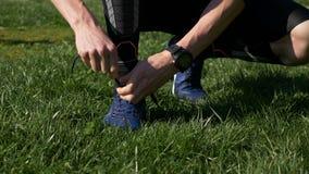 Nahaufnahme des Athletenmannes Spitzee bevor dem Rütteln im Park binden stock video footage