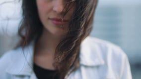 Nahaufnahme des attraktiven braunhaarigen Mädchens in den hellblauen Jeans beschichten mit schönem Make-up mit dem beeinflussende stock footage