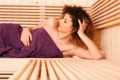 Nahaufnahme des attraktiven Frauenlügens entspannte sich an der Sauna Lizenzfreie Stockbilder