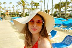 Nahaufnahme des attraktiven Mädchens mit dem langen Haar, das auf dem Strand steht Das Mädchen, das zur Kamera lächelt und zeigt  Lizenzfreie Stockbilder