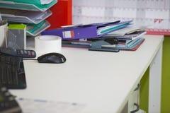 Nahaufnahme des aus dem wirklichem Leben unordentlichen Schreibtisches im Büro Stockbilder