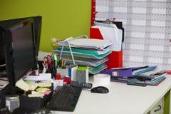 Nahaufnahme des aus dem wirklichem Leben unordentlichen Schreibtisches im Büro Stockfotografie