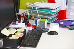 Nahaufnahme des aus dem wirklichem Leben unordentlichen Schreibtisches im Büro Stockfoto