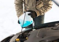 Nahaufnahme des auslaufenden Frostschutzmittels des Mannes in Wasserbehälter Stockbilder