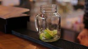 Nahaufnahme des Barmixers Mojito-Cocktails mit Kalk, Minze und Rum in der Bar machend stock video