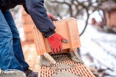 Nahaufnahme des Bauarbeiters, Maurer, der neues Haus mit Ziegelsteinen baut Lizenzfreie Stockfotos