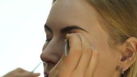 Nahaufnahme des Berufsmake-upkünstlers, der tägliches Make-up tut, setzt Pulver auf die Backen der Frau mit Bürste stock footage