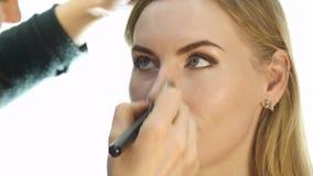Nahaufnahme des Berufsmake-upkünstlers, der tägliches Make-up tut, setzt Pulver auf die Backen der Frau mit Bürste stock video footage
