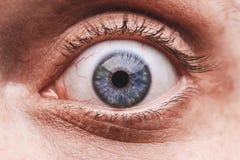 Nahaufnahme des blauen Auges des überraschten Mannes Stockbilder