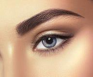 Nahaufnahme des blauen Auges der jungen Frau Makroauge, das oben, lokalisiert auf Weiß schaut Lizenzfreie Stockfotos