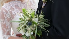 Nahaufnahme des bohho Hochzeitsblumenstraußes in den Händen der Braut und des Bräutigams stock footage