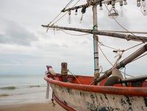 Nahaufnahme des Bootskopfes des Fischerbootes des Kalmars und der Glühlampe auf dem Strand am bewölkten Morgentag stockfotografie