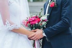 Nahaufnahme des Bräutigams, der die Braut durch die Hände hält stockfotografie