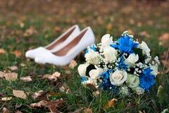 Nahaufnahme des Brautgelbrosenblumenstraußes auf Hintergrund ihrer Weißschuhe auf grünem Gras Stockfoto