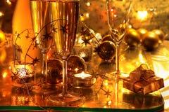 Nahaufnahme des Champagners, Kerze auf Goldhintergrund. Stockbild