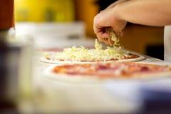 Nahaufnahme des Chefbäckers in der weißen einheitlichen Herstellungspizza in der Küche Stockbilder