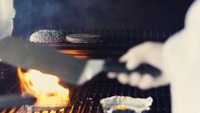 Nahaufnahme des Chefs Ei und Kotelett für schwarzen Burger auf Grill an der Restaurantküche zuhause zubereitend Stockbild