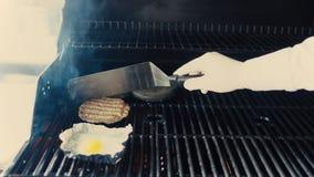 Nahaufnahme des Chefs Ei und Kotelett für schwarzen Burger auf Grill an der Restaurantküche zuhause zubereitend Stockfotografie
