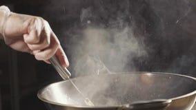 Nahaufnahme des Chefs Fleisch in der Wokwanne kochend Fleisch gebraten in der Blutgeschwürbutter, Zeitlupe stock video