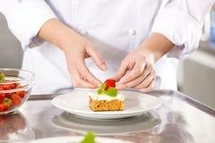 Nahaufnahme des Chefs Nachtischkuchen mit Erdbeere verzierend Stockfotos