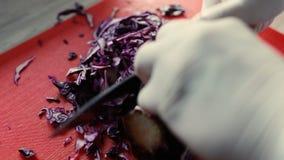 Nahaufnahme des Chefs schnitt Kohl für Teller auf Küchenbrett stock footage