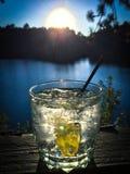 Nahaufnahme des Cocktails bei dem Sonnenuntergang, der reizenden blauen See übersieht stockfoto