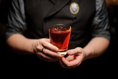 Nahaufnahme des Cocktails mit orange Rinde in den Händen des Barmixers lizenzfreie stockbilder