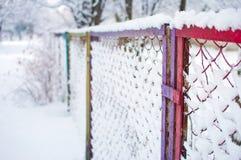 Nahaufnahme des colorfu Maschenzauns bedeckt im Schnee Lizenzfreie Stockbilder