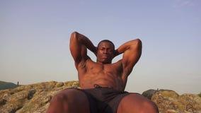 Nahaufnahme des erschöpften Afroamerikanerbodybuilders, der Presse tut, ups Perfekter muskulöser Körper Ausbildung im Freien, Ber stock video