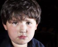 Nahaufnahme des erschrockenen Jungen gegen einen schwarzen Hintergrund Stockfotos
