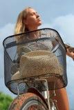 Nahaufnahme des Fahrradkorbes mit einem Hut hielt durch eine junge blonde Frau Lizenzfreie Stockfotos