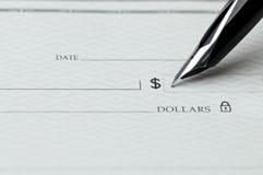 Nahaufnahme des Federschreibens auf einem unbelegten Bankscheck Lizenzfreie Stockfotografie