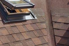 Nahaufnahme des Fensteroberlichtes auf einem Dach mit Asphalt Shingles oder Bitumen deckt im Bau mit Ziegeln Stockbilder