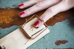 Nahaufnahme des Fingers der Frau in der Mausefalle Stockbilder