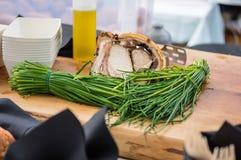 Nahaufnahme des Fleisches und der Schnittlauche auf dem hölzernen Hintergrund am offenen Lebensmittelmarkt in Ljubljana, Slowenie Stockbild