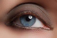 Nahaufnahme des Frauenauges mit schönem braunem smokey mustert Make-up stockbild