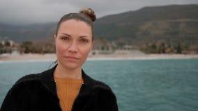 Nahaufnahme des Frauengesichtes auf dem Ufer von See, untersuchend Kamera stock footage