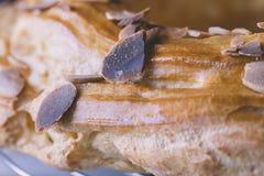Nahaufnahme des frisch gebackenen köstlichen profiterole umfasst mit choc Stockfotos
