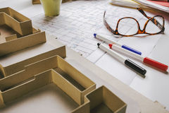 Nahaufnahme des Gebäudemodells und Entwurfswerkzeuge auf einem Bau planen. Lizenzfreie Stockfotografie