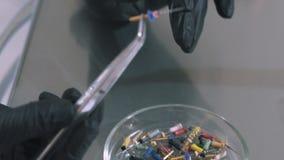 Nahaufnahme des geernteten Rahmens ist eine Schüssel mit Düsebohrgeräten auf dem Bohrgerät Der Zahnarzt in den sterilen Handschuh stock video