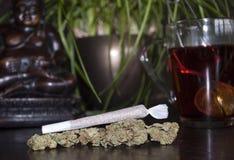 Nahaufnahme des gerollten Marihuanaunkrautgelenkes und Knospen auf hölzernem Hintergrund, mit Buddha-Statuette stockfotografie