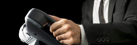 Nahaufnahme des Geschäftsmannes ein schwarzes Überlandleitungstelefon bezüglich aufhebend Stockbild