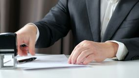 Nahaufnahme des Geschäftsmannes Hand Signing und Drücken eines Stempels auf Dokument im Büro stock footage